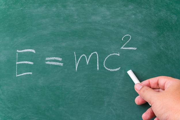 Main d'homme écrivant la formule de relativité sur le tableau vert