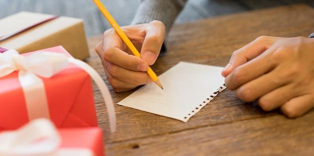 Main d'homme écrivant sur papier pour liste de souhaits sur un bureau en bois avec boîte-cadeau