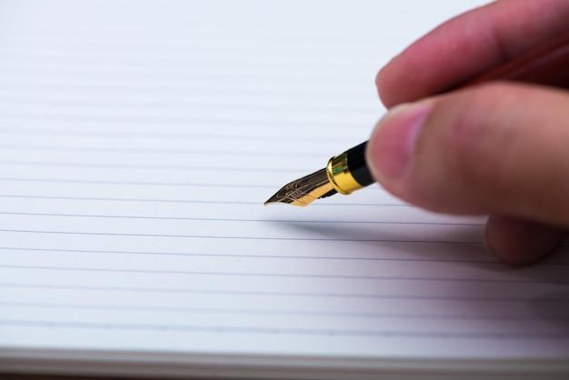 Main d'homme écrivant avec un stylo plume ou un stylo à encre avec du papier pour ordinateur portable
