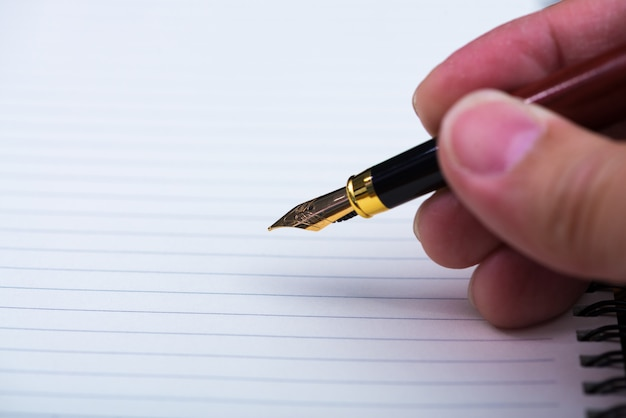 Main d'homme écrivant avec un stylo plume ou un stylo à encre avec ordinateur portable