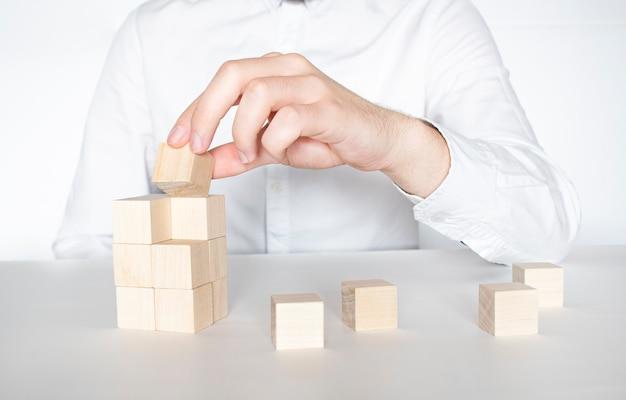 La main de l'homme empilant des blocs de bois. concept de développement des affaires.