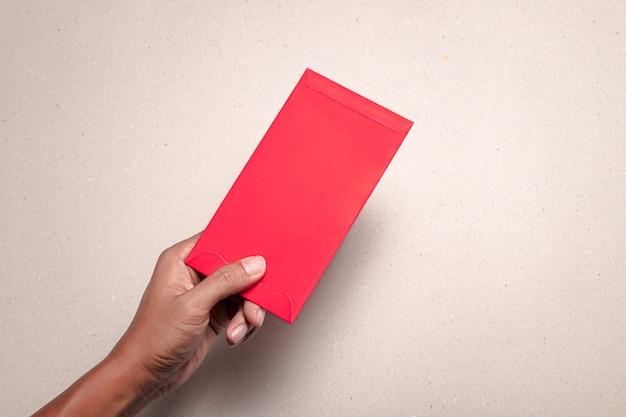 Main de l'homme avec enveloppe rouge chinoise