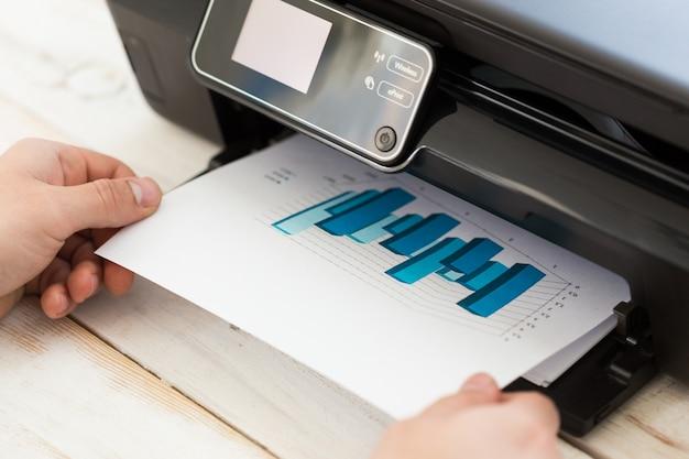 Main de l'homme faisant des copies. travailler avec une imprimante