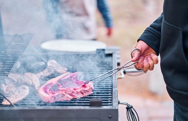 La main de l'homme fait cuire un gros steak de boeuf sur le barbecue.