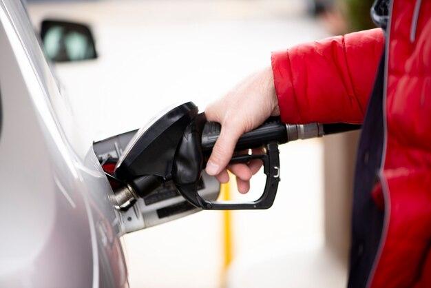 La main de l'homme fait le plein de gaz ou d'huile dans la station de ravitaillement préparer le transport pour voyager