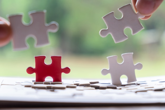 Main d'un homme ou d'une femme mettant un puzzle à brancher sur un bureau en bois et sur la nature