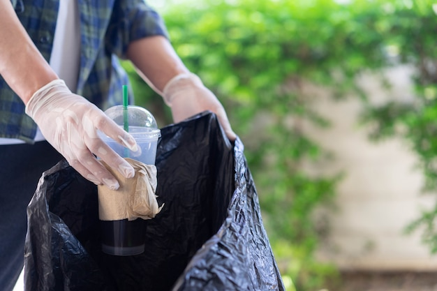 Main de l'homme avec des gants tenant des ordures à jeter dans un sac noir pour le concept de la journée mondiale de l'environnement