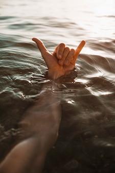 Main de l'homme avec un geste de shaka dans l'eau