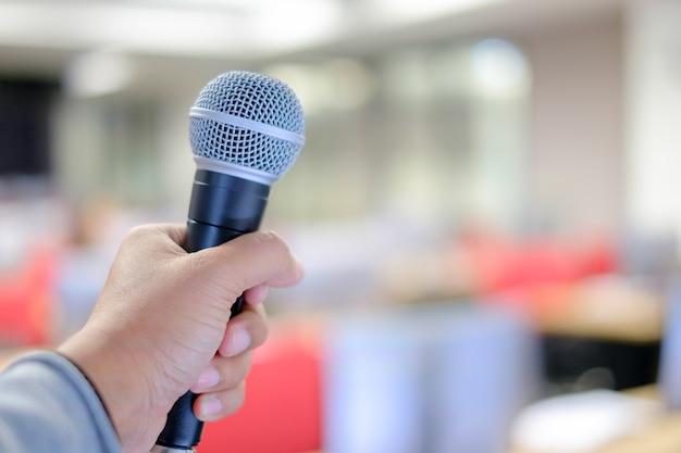Main de l'homme instructeur tenant le microphone pour la formation dans la salle de classe informatique.