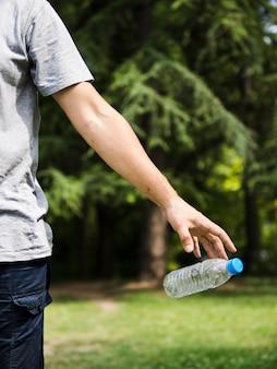 Main d'homme jetant une bouteille d'eau en plastique dans le parc