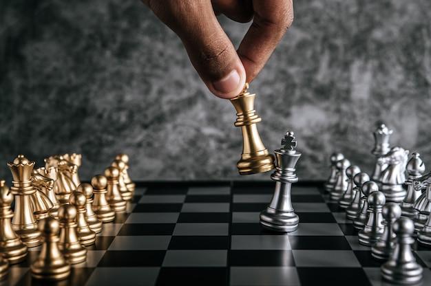 Main d'un homme jouant aux échecs pour la planification d'entreprise et la comparaison de métaphore, mise au point sélective