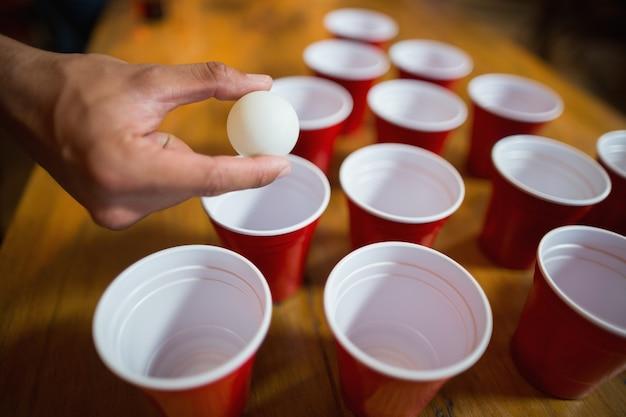 Main de l'homme jouant de la bière pong