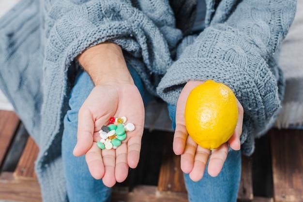 Main de l'homme malade montrant des pilules multicolores et citron entier