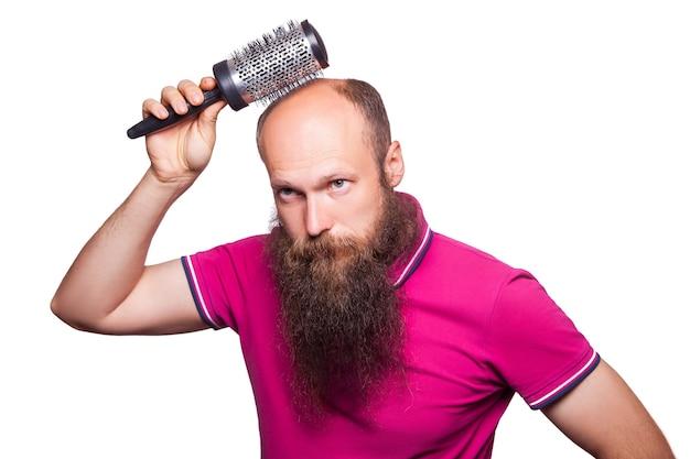 Main d'homme malheureux adulte tenant le peigne sur la tête chauve