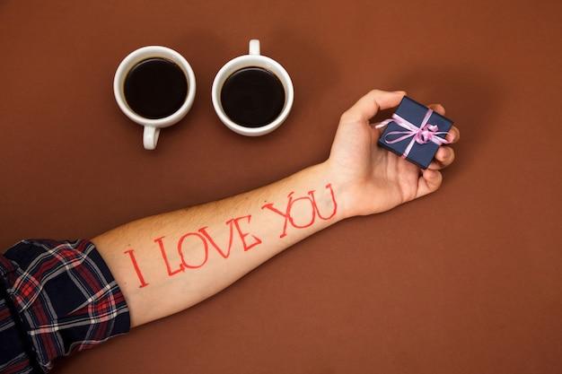La main de l'homme sur marron avec cadeau et panneau rouge je t'aime.