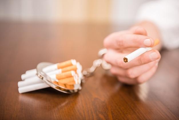 Main de l'homme avec des menottes et des cigarettes sur la table.