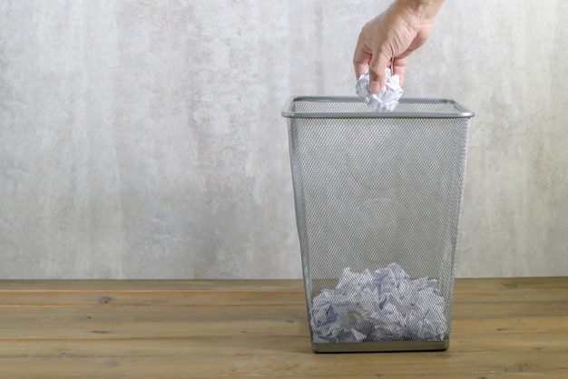 Main homme mettant du papier froissé à la poubelle