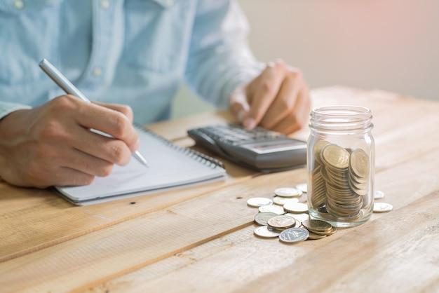 La main de l'homme mettant la pièce dans le verre et l'écriture sur le cahier sur la table de travail en bois avec pile de pièces - investissement, affaires, finance et banque