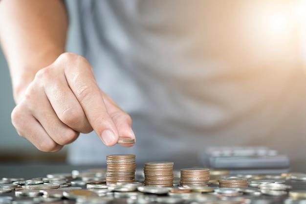 Main de l'homme mettant des pièces de monnaie s'empilant pour les entreprises de croissance et épargne concept.