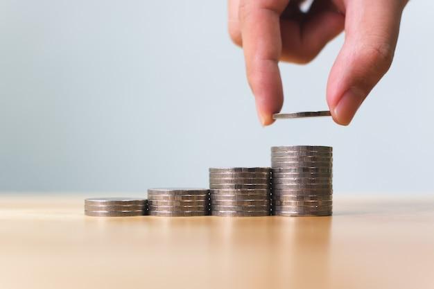 Main de l'homme mettant la pile de pièces de monnaie étape de plus en plus de valeur de croissance