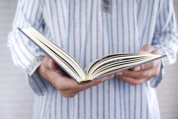 Main d'homme musulman tenant le livre saint coran avec espace copie