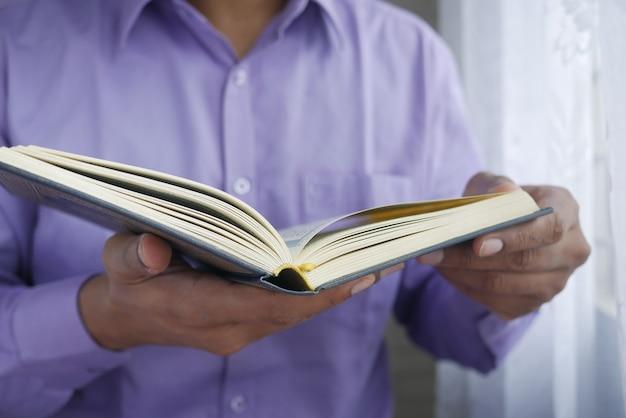 Main d'homme musulman tenant le livre saint coran avec espace de copie