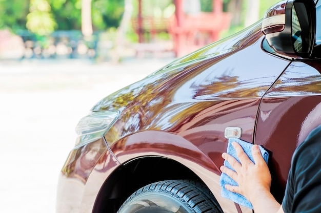 La main de l'homme nettoie et cire la voiture