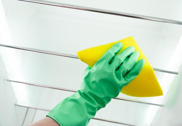 La main de l'homme nettoie le réfrigérateur de la cuisine