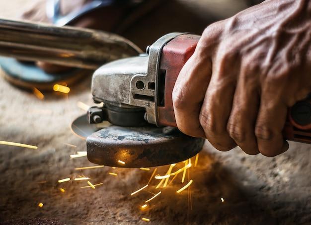 Main de l'homme avec l'outil de coupe en acier flou sur fond noir