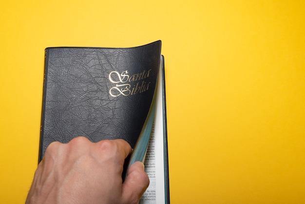 Main de l'homme ouvrant santa biblia ou sainte bible sur jaune