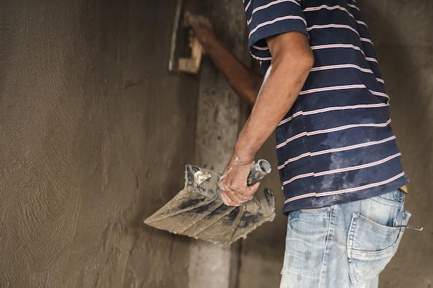 La main de l'homme ouvrier plâtrant un mur avec une truelle
