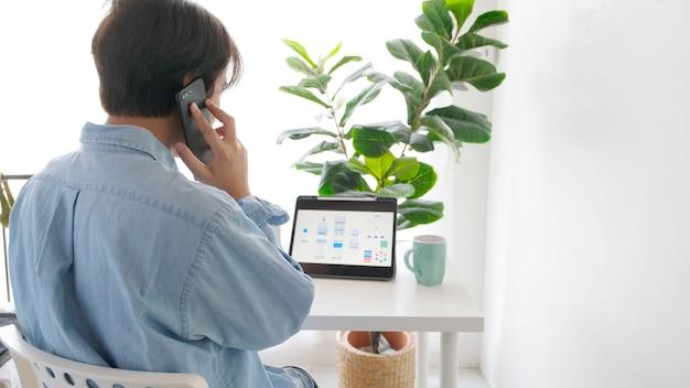 Main d'homme parlant au téléphone tout en travaillant avec une tablette numérique pour un prototype de développement d'applications mobiles au bureau à domicile