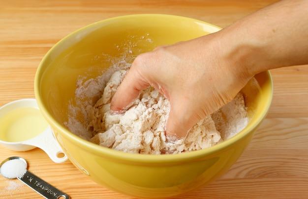 Main de l'homme pétrir la pâte à pain dans le bol de mixage