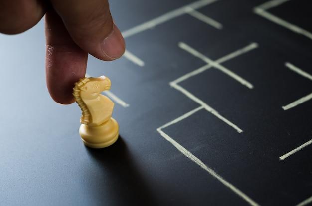 La main de l'homme place les échecs du chevalier au labyrinthe