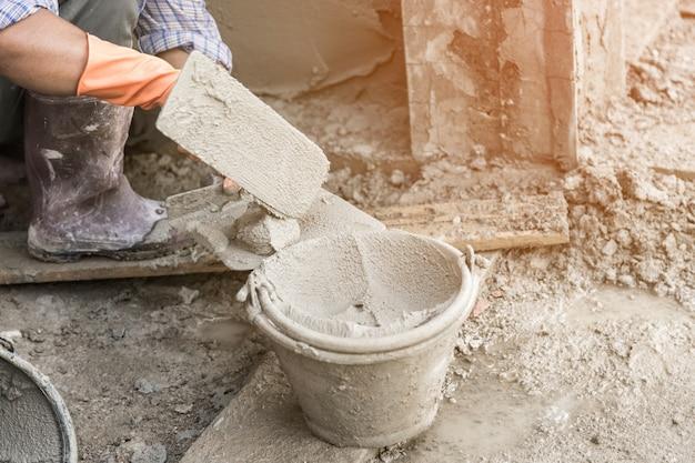 La main de l'homme en plâtrant un mur avec une truelle.