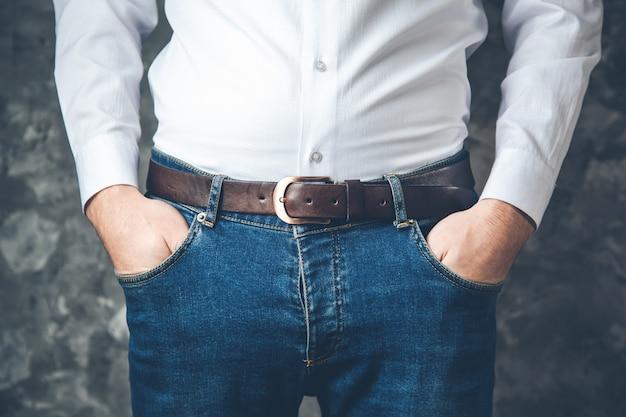 Main de l'homme sur la poche sur fond gris