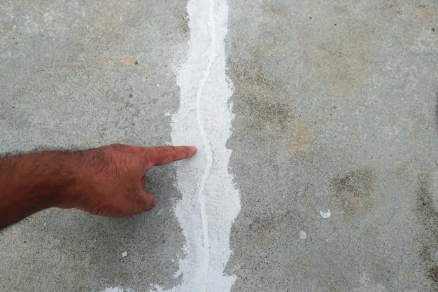 Main de l'homme pointant vers le sol fissuré problème de construction et concept de solution gros plan