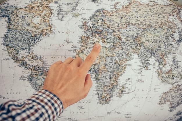 La main d'un homme pointe vers la carte, en gros plan.
