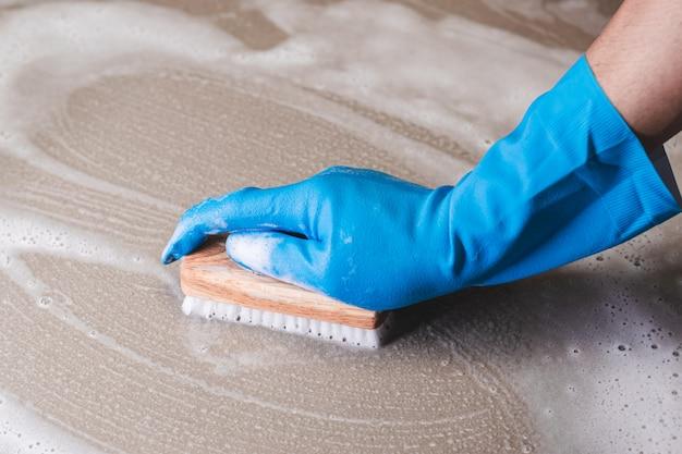 La main d'un homme portant des gants en caoutchouc bleu est utilisée pour convertir le nettoyage à la brosse sur le sol en carrelage.