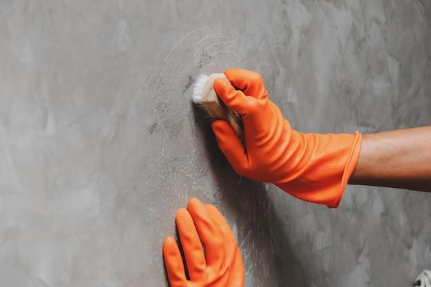 Main de l'homme portant des gants en caoutchouc orange pour convertir le nettoyage des broussailles