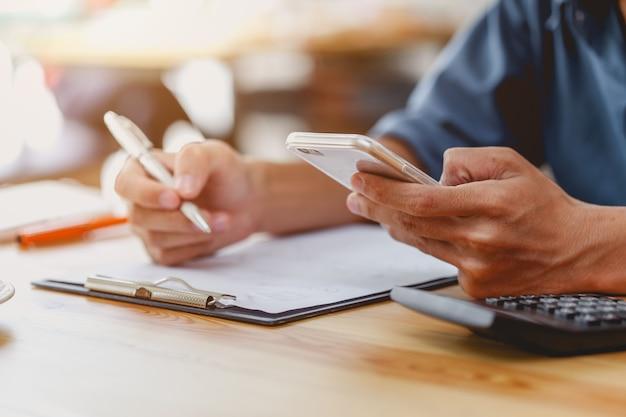 Main de l'homme prenant des notes d'information et de recherche dans le smartphone mobile.