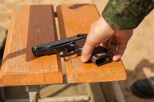 La main d'un homme prend un fusil