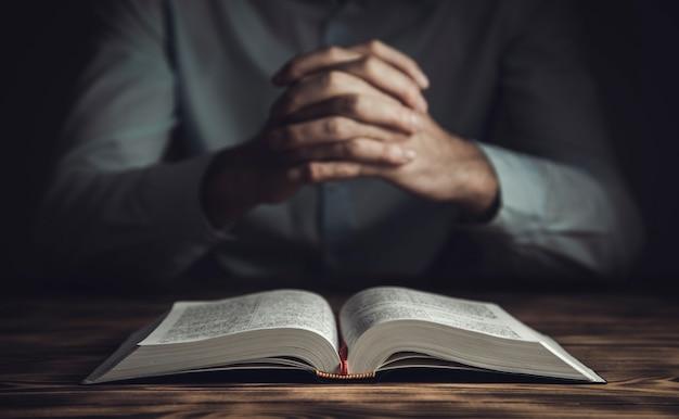 La main de l'homme de prière sur la bible sur la pièce sombre