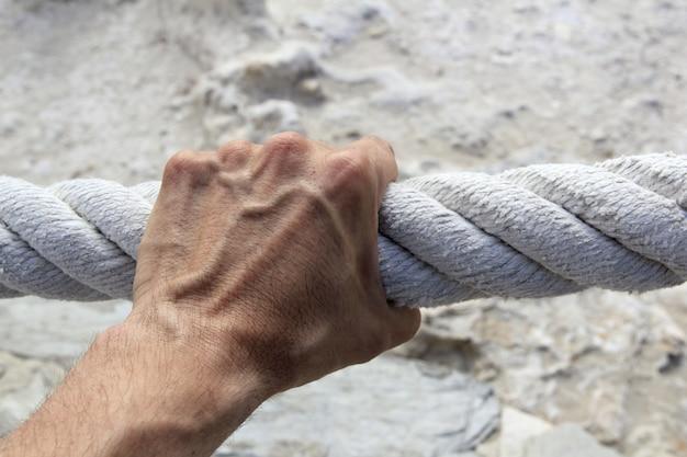 Main d'homme prise forte grosse corde âgée