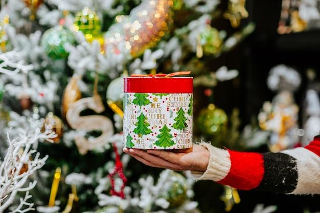 La main de l'homme en pull d'hiver rouge et noir tenant la boîte de cadeau de noël contre l'arbre de noël.