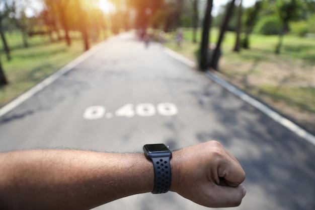 Main d'homme regardant montre intelligente en faisant du jogging dans le parc