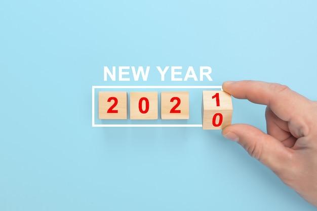 Main de l'homme retournant des cubes avec l'année 2020 à 2021.
