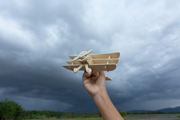 Main de l'homme avec sa main exécute le modèle de l'avion dans le nuage d'orage du ciel.