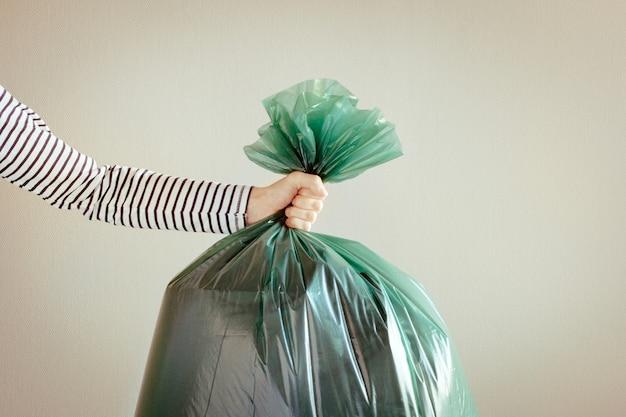 Main de l'homme avec sac poubelle vert. fond neutre.