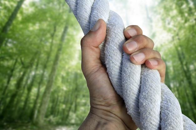 Main d'homme saisissant la corde de forêt verte